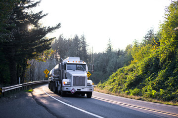 Big rig semi truck with tank trailers on winding road in forest