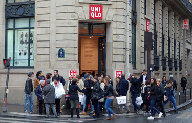 Customers leave the casual clothing store Uniqlo operated by Japan's Fast Retailing in Paris, France