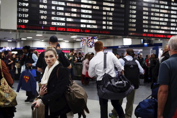 Travelers wait for their train at Pennsylvania Station the day before Christmas in New York