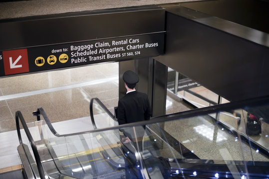 Pilot goes down with suitcase on airport escalator