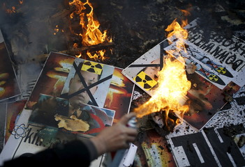 A protester burns banners depicting North Korean leader Kim Jong Un during an anti-North Korea rally in central Seoul