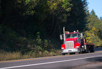 Red semi truck with flat bed trailer on forest road