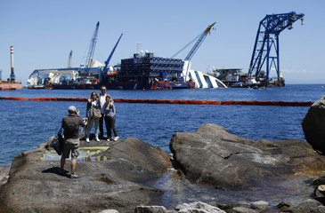 People take a picture in front of the capsized cruise liner Costa Concordia lies surrounded by cranes outside Giglio harbour