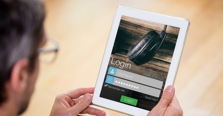 Man holding digital tablet with login text