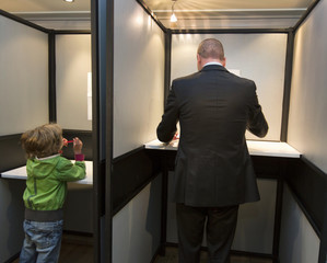 Socialist Party Leader Diederik Samsom casts his ballot for the Netherlands' general election as his son Fana (L) plays with a red pencil at a voting booth in Leiden