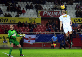 Malaga's goalkeeper Caballero looks at Sevilla's Negredo during a soccer match in Seville