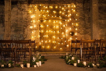 Wedding ceremony decorations in loft grunge surround. Light bulb garland, candles, glass and chairs