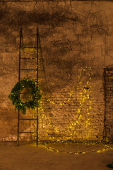 Decor in loft style with garlands of light bulbs, coniferous wreath and stairs against the backdrop of a scuffed wall of plaster and old brick