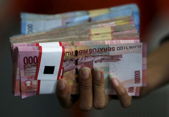 An employee of a money changer holds a stack of Indonesia rupiah notes before giving it to a customer in Jakarta