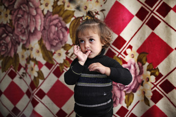 A Syrian refugee baby is seen inside her family tent at Bib Salam refugee camp in Syria