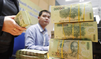 Employees count money at a branch of the BIDV in Hanoi