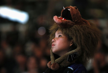 Kings' fan Rose wears the Kings' lion mascot on her head as she waits for Game 6 of their NHL Western Conference quarter finals hockey playoff against the St. Louis Blues to start in Los Angeles