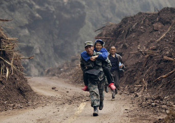 Chinese People's Liberation Army soldier, carries survivor as he runs down stretch of road to Lingguan township which was recently cleared of debris from landslides caused by earthquake, in Baoxing county