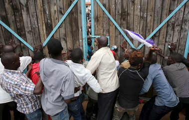 Supporters of opposition leader Kizza Besigye try to stop police to enter his office in Kampala