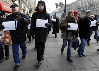 People hold white sheets of paper as they walk along Nevskiy Avenue during a protest action in St. Petersburg