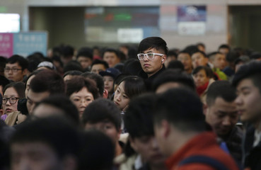 Passengers wait to board a train to Xi'an, at the Beijing West Railway Station