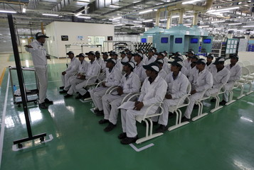 File photo of an instructor teaching newly appointed workers during a media tour to the newly inaugurated Honda Motorcycle & Scooter India plant at Vithalapur