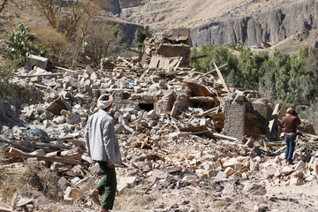 People walk on the rubble of a house destroyed by a Saudi-led air strike in Sanaa