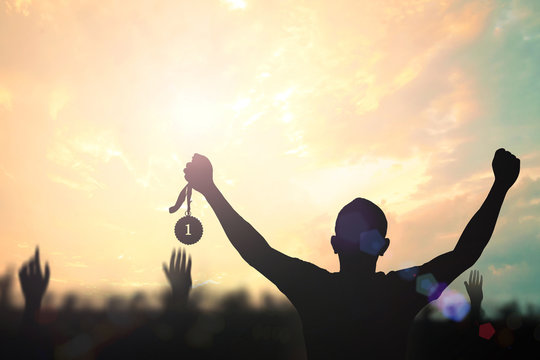 Victory concept: Silhouette human hand holding gold medal against colorful autumn sunset sky