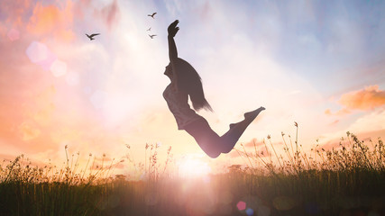 Freedom concept: Silhouette of a girl jumping at sunset meadow with her hands raised.
