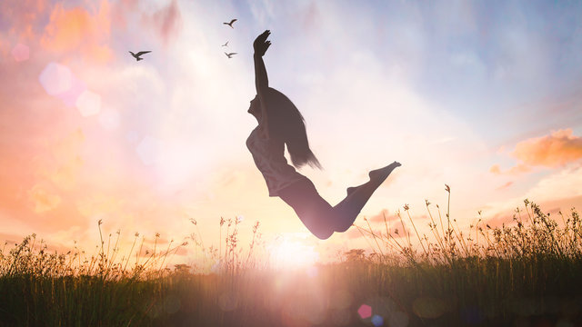 World mental health day concept: Silhouette of a girl jumping at autumn sunset meadow with her hands raised