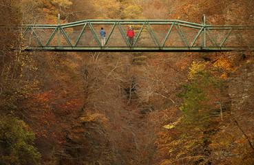 People stop on a bridge over the River Garry to view the autumn scene near Killiecrankie in Scotland