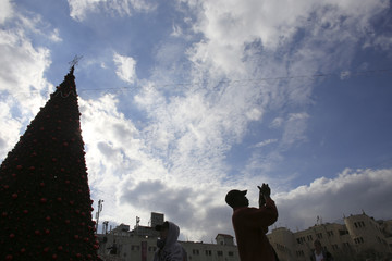 A tourist takes a picture near a Christmas tree outside the Church of the Nativity in Bethlehem