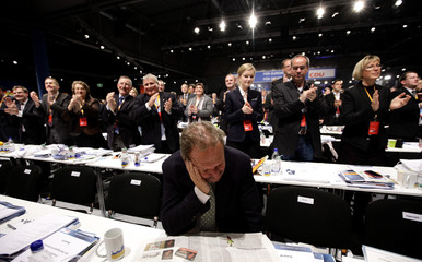 """German public sector union """"Verdi"""" leader Frank Bsirske looks down as delegates applaud after the speech of German finance minister Wolfgang Schaeuble of Germany's conservative Christian Democratic Union (CDU) during the party convention in Leipzig"""