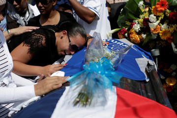 Angela Martinez, mother of Yordano Ventura's daughter, cries on the coffin during the funeral at the Municipal Baseball Stadium of Las Terrenas, Dominican Republic