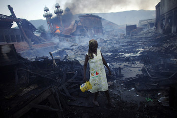 A woman walks near a fire at the Hyppolite iron market in downtown Port-au-Prince