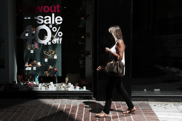 A woman walks in front of a shop window during summer sales season at a commercial street of Athens