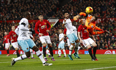 West Ham United's Adrian makes a save as Manchester United's Wayne Rooney (L) looks on