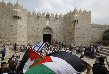 Palestinians wave flags as Israeli youths gather in front of the Damascus Gate in Jerusalem's Old City