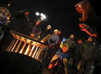 People warm themselves during an anti-government rally in central Kiev