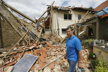 Resident Loleit stands in the rubble of the kitchen of his destryoed house following a Tornado in Framersheim