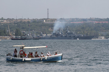 People sail a motor boat, with Russian warships seen in the background, in Sevastopol