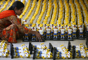 A worker arranges models of the mascot of the Commonwealth Games before packing them in a factory at Mohali