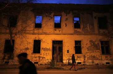 People walk next to destroyed houses in Mostar