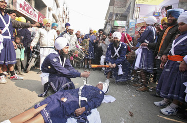 A Sikh performer breaks coconut with stick during religious procession on eve of birth anniversary of Guru Gobind Singh in Amritsar