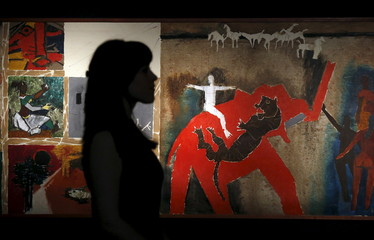 """A staff member poses with """"Untitled"""" from 1956 by Maqbool Fida Husain at Christie's auction house in London"""