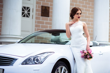 gorgeous bride with fashion makeup and hairstyle in a luxury wedding dress near white cabriolet car