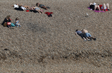 People sunbathe by the sea on a sunny day on Brighton Beach in southern England