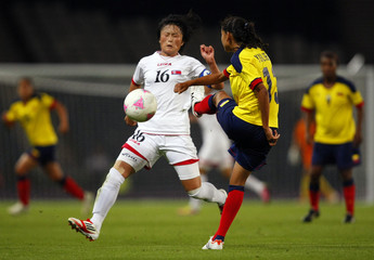 North Korea's Kim Song-Hui and Colombia's Yulieht Dominguez fight for the ball during their women's Group G football match at the London 2012 Olympic Games in Hampden Park, Glasgow, Scotland