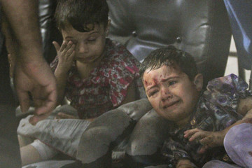 Injured children react in a field hospital after what activists say were air strikes by forces loyal to Syria's President Assad in Douma