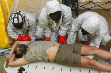 Rescuers wearing anti-radiation suit examine a mock victim exposed to radiation during an earthquake drill in military Camp Aguinaldo in Quezon city, Metro Manila