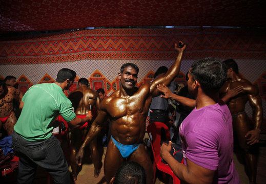 A competitor has tanning lotion applied on his body before his turn during a body building competition in Mumbai