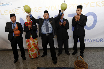 """Mat Zin, a local well-known """"bomoh"""", holds two coconuts as he performs a ritual to help finding missing Malaysia Airlines MH370 at Kuala Lumpur International Airport"""