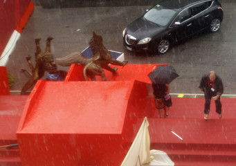 People walk under the rain near toppled Golden Lions, a symbol of the Venice Film Festival, during the festival