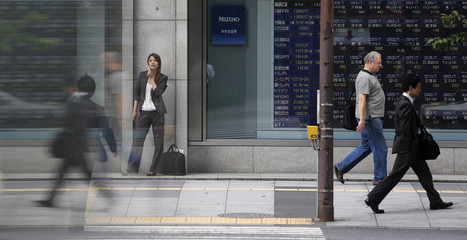 Pedestrians walk past a stock quotation board displaying stock prices outside a brokerage, in Tokyo