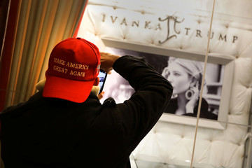 """A man wearing a """"Make America Great Again"""" cap takes a picture of Ivanka Trump jewelry display window inside Trump Tower in New York City"""